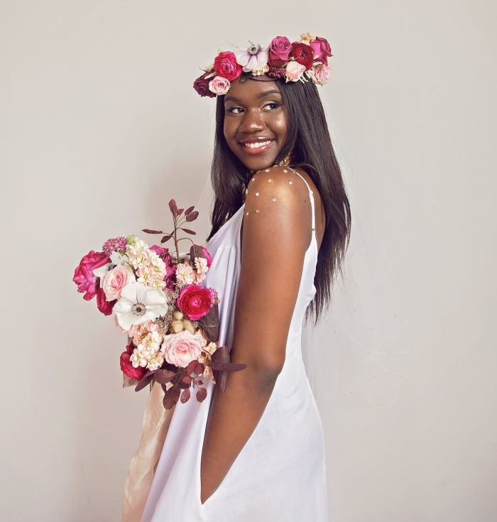 Image of a dark skinned woman in a white dress with wedding flowers and crown